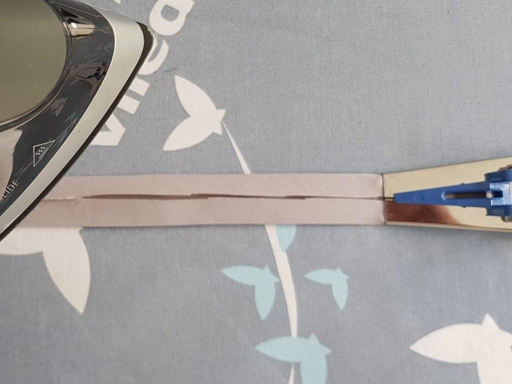 Le pliage du biais au fer à l'aide de l'appareil à biais.