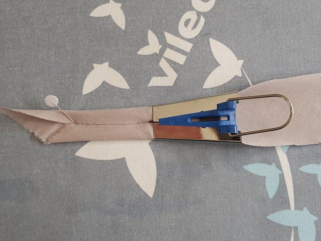 Épingler l'extrémité du ruban de biais sur la table à repasser pour utiliser l'appareil à biais.