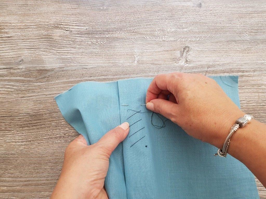 Réalisation du point de bâti en diagonale pour maintenir les plis pendant la réalisation de l'ouvrage