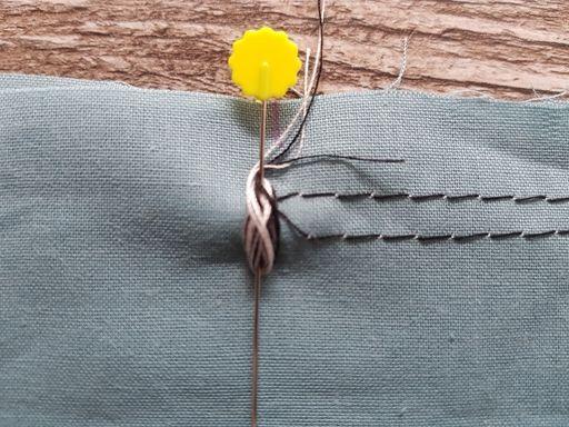 Maintient des fils de couture  enroulés en huit autour d'une épingle au départ des fronces
