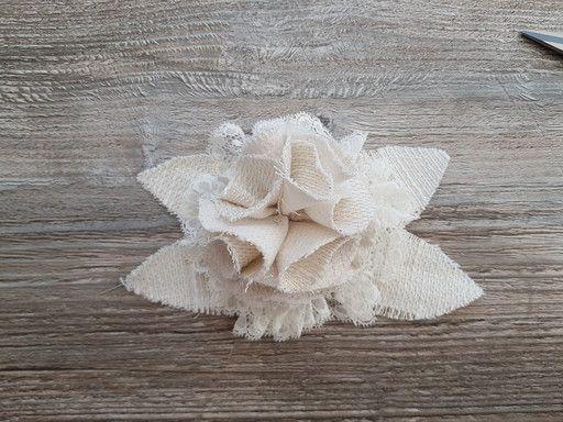 Fleur réalisée dans un tissu tissé. Elle est idéale pour orner un vêtement ou un accessoire.