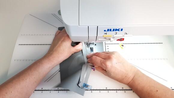 Au milieu de l'assemblage, mettre l'aiguille en position basse, lever le pied presseur et faire glisser le curseur de la fermeture afin de ne pas être gêné par son volume à la fin de la couture.